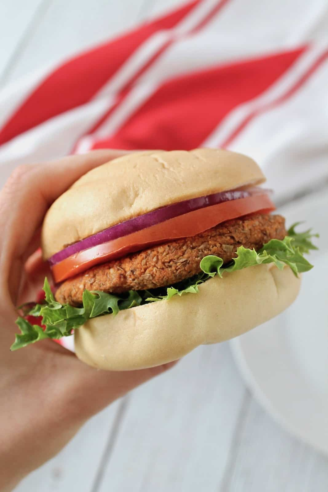 Close up of hand holding a lentil burger with lettuce, tomato, onion and a bun with a red and white striped dish towel in the background