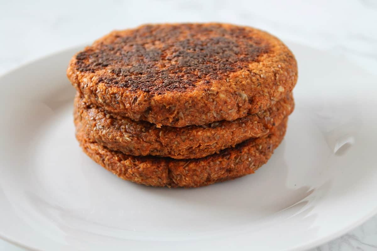 Three stacked cooked sprouted lentil patties on a white plate