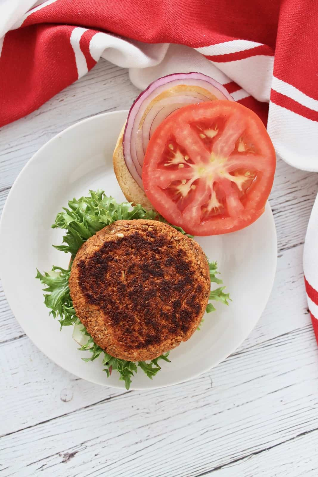 Overhead shot of open faced sprouted lentil burger on green lettuce on a bun on a white plate with tomato and onion next to it on a white plate next to a red and white striped dish towel