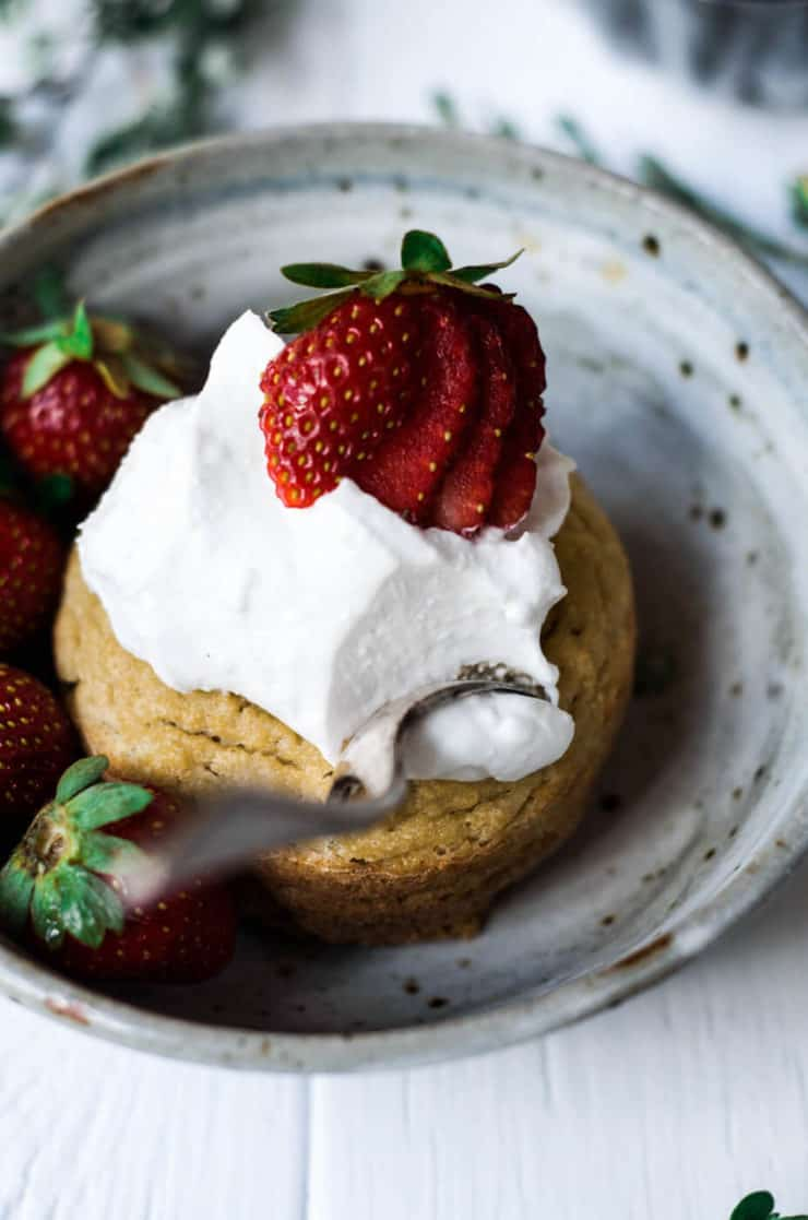 Grey ceramic bowl with yellow cake inside topped with white whipped cream and strawberries
