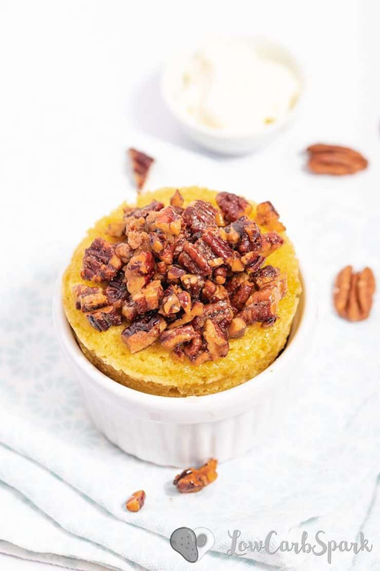 White ramekin with yellow cake inside topped with chopped pecans on a white surface with pecans next to it