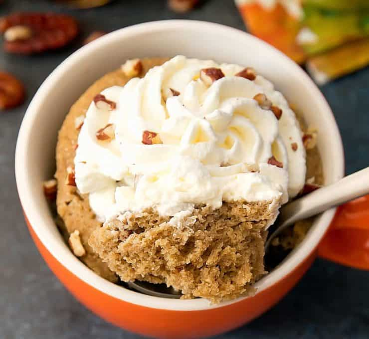 Orange and white ramekin filled with brown cake topped with a spoon takin a bite out with swirled whipped cream with chopped pecans on top