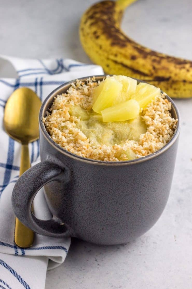Grey mug with cake inside topped with coconut and pineapple chunks with a gold spoon and blue and white plaid dish towel and banana next to it