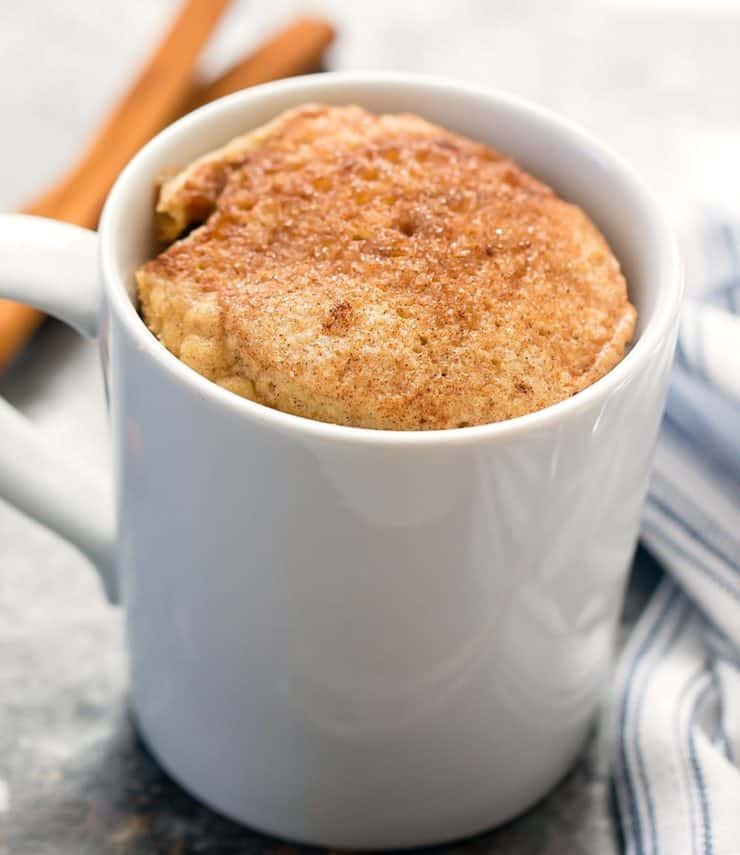 White mug filled with yellow cake topped with cinnamon on a grey surface next to a blue and white striped dish towel next to cinnamon sticks