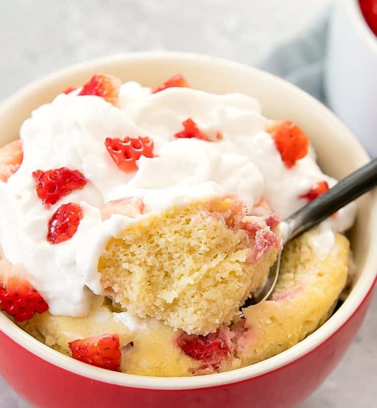 Close up of red and white ramekin filled with yellow cake topped with whipped cream and chopped strawberries with a spoon taking a scoop out of the cake