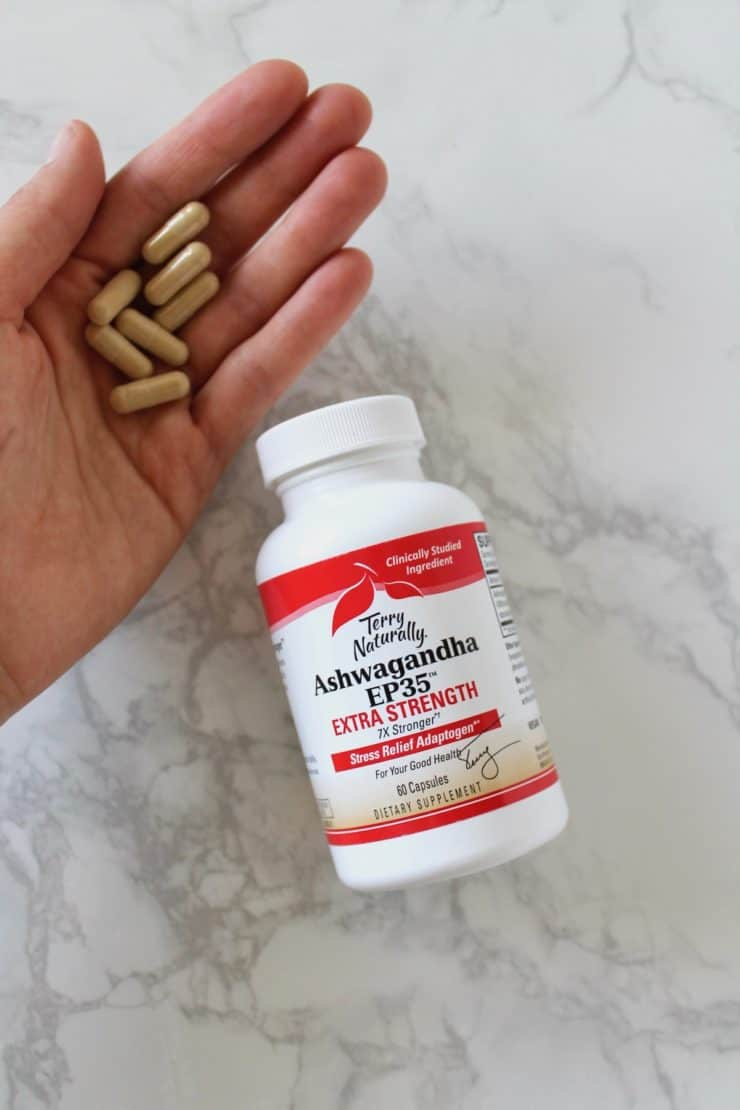 Red and white ashwaganda supplement bottle laying flat on a marble surface next to a hand holding loose supplement capsules
