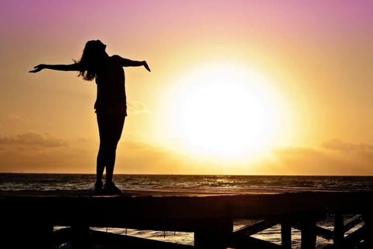 Silhouette of woman standing on wooden dock with sunset, sun and ocean behind her